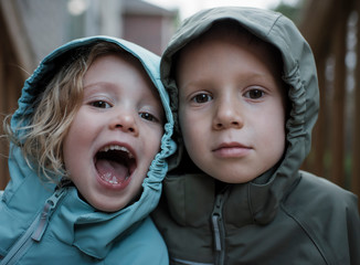 Close-up portrait of siblings in raincoats standing outdoors