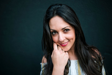 Close-up portrait of smiling woman standing against wall