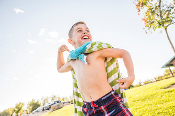 Low angle view of happy shirtless boy with towel flexing muscles while standing against sky at park
