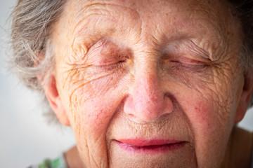 Close-up of sad senior woman with eyes closed