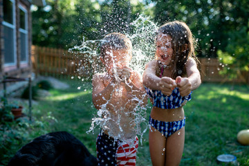 Cheerful siblings bursting water bombs while standing at backyard