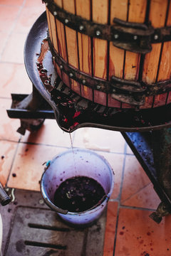 High angle view of wine filling in bucket from cask at factory