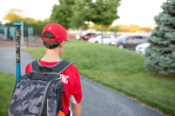 Rear view of baseball player with backpack standing in field