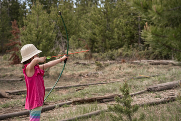 Side view of girl in hat aiming with bow and arrow in forest