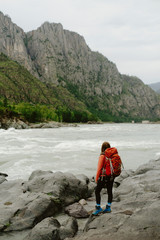 Side view of female hiker with backpack standing on rocks at riverbank against sky