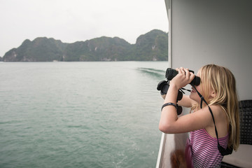 Side view of girl looking through binoculars while standing in boat on sea against sky