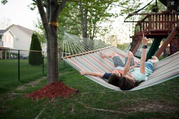 Siblings talking while relaxing on hammock at yard