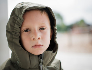 Close-up portrait of cute boy wearing raincoat against window at home