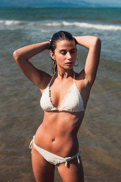 Woman with hand in hair wearing white bikini while standing at beach during sunny day
