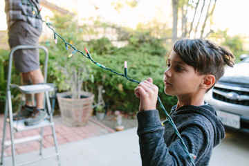 Son assisting father in hanging colorful string lights during Christmas
