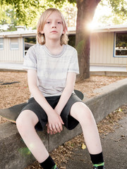 Portrait of boy with skateboard sitting on retaining wall at park