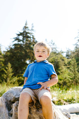 Portrait of boy sitting on rock against clear sky during sunny day at Fort Ebey State Park