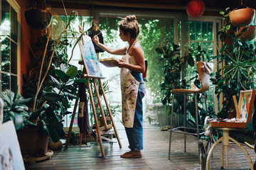 Side view of female artist painting on canvas while standing in art studio