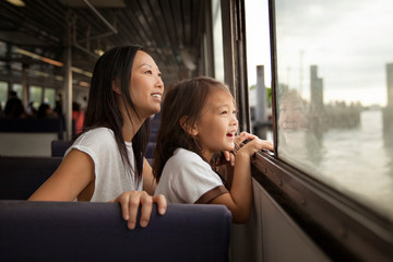 Smiling mother and daughter looking through window in ferry