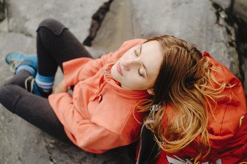 High angle view of female hiker with eyes closed reclining on backpack