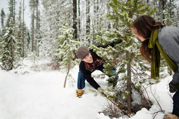 Happy boyfriend looking at girlfriend while cutting pine trees in snow covered forest