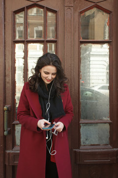 Smiling young woman using smartphone near door