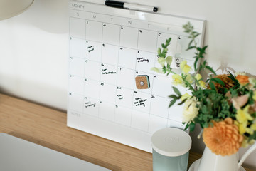 High angle view of calendar with text by flower vase on desk in office