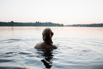 Rear view of topless woman swimming in river against clear sky during sunset