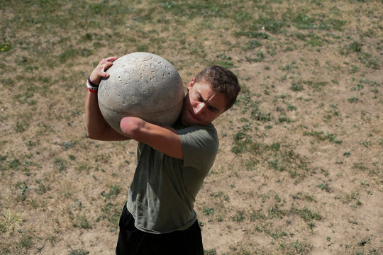 High angle view of male athlete carrying atlas stone