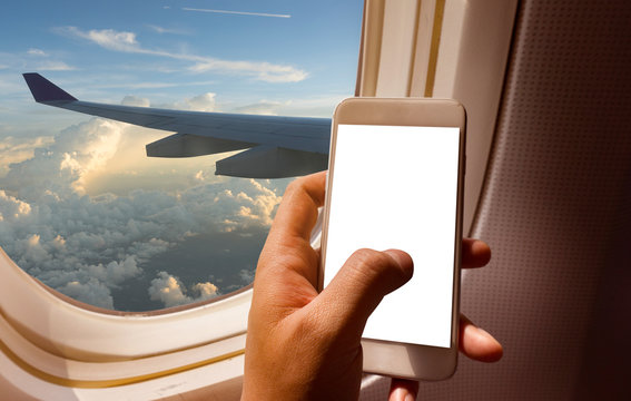 hand holding mobile phone with blank screen neary window seat in airplane