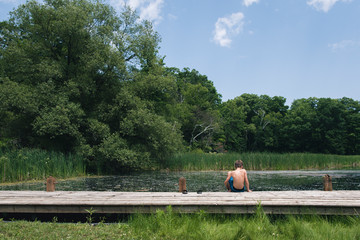 Rear view of shirtless boy sitting on pier over lake against sky in forest
