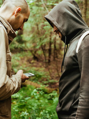 Friends using smart phone for direction in forest