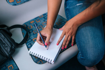 Midsection of woman writing on diary while sitting in bus