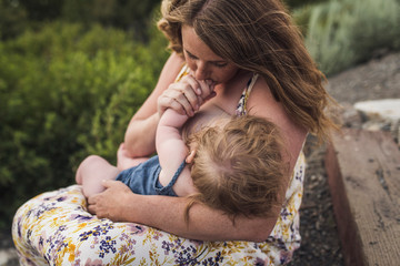 Mother breastfeeding daughter while sitting against plants in forest