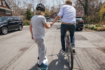 Rear view of father riding bicycle while assisting son in skateboarding on road