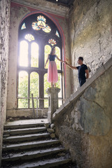 Ballerina standing on newel post while holding male friend's hand in old building