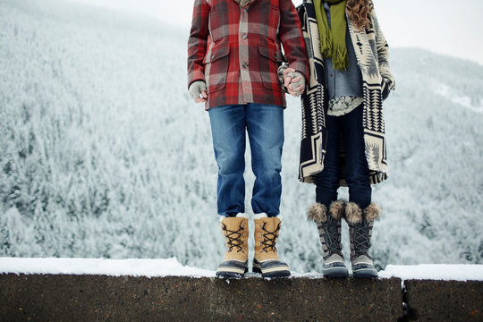 Low section of couple holding hands while standing on retaining wall