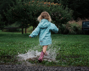 Rear view of playful girl splashing water in puddle at apple orchard