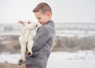 Boy carrying lamb on farm during winter