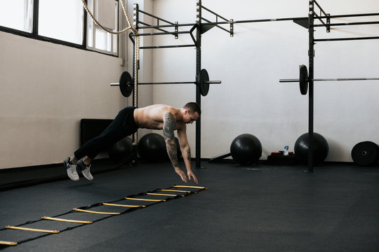 Full length of shirtless young man using agility ladder while exercising in gym
