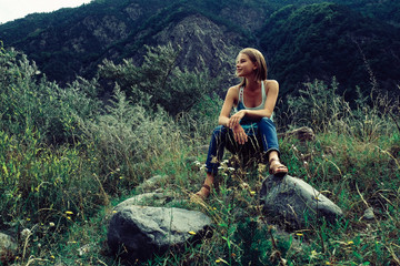 Low angle view of woman looking away while sitting on grassy field against mountain