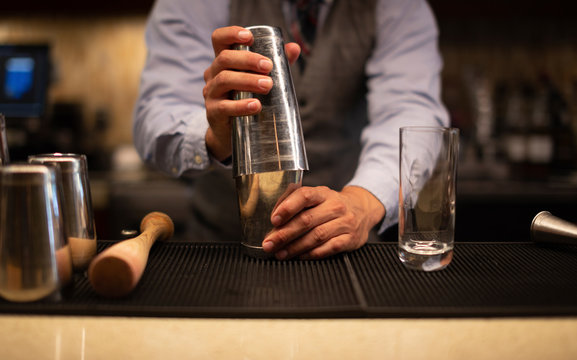 Midsection of bartender mixing drink in glass on bar counter