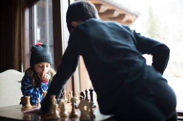 Siblings playing chess while standing by window at home