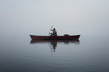 Woman rowing boat on river at Algonquin Provincial Park during foggy weather