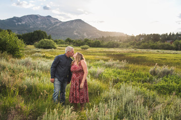 Romantic couple kissing while standing on grassy field against sky in forest