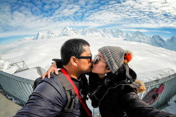 Young sweet couple taking kissing selfie with the view of the Swiss Skyline from Schilthorn, Switzerland