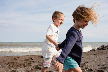 Happy siblings holding hands while walking at beach against sky during sunny day