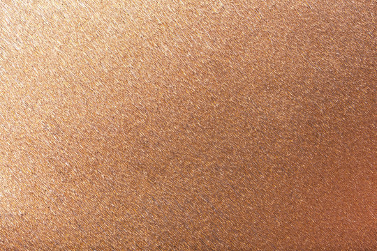 Textural of bronze background of wavy corrugated paper, closeup.