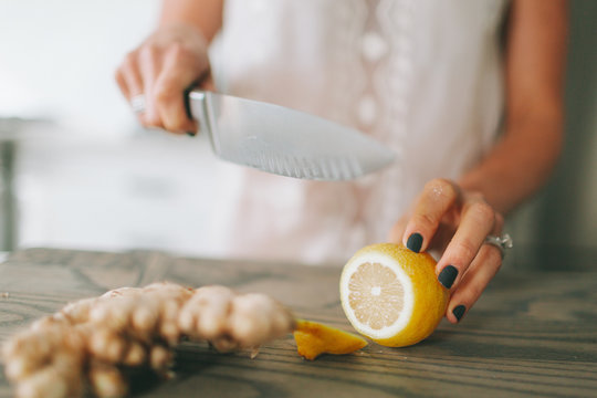 A woman cutting lemon and ginger on a cutting board.
