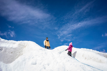 Low angle view of father with daughter standing on snow covered hill against blue sky during sunny day
