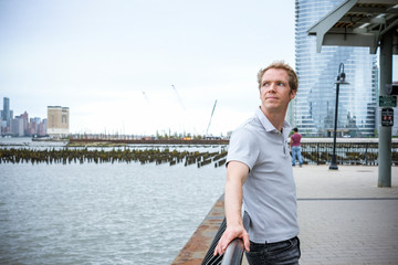Side view of thoughtful man looking away while standing by river on promenade against sky in city