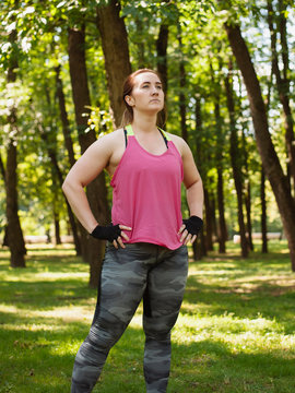 Confident woman with hands on hip exercising on grassy field against trees at park