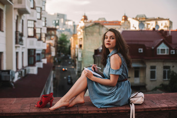 Side view portrait of confident young woman with notepad sitting on retaining wall against buildings in city