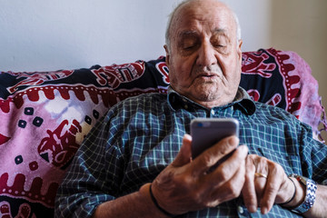 Senior man using mobile phone while relaxing on sofa at home