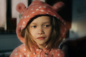 Close-up of thoughtful girl in pink hooded jacket looking away while sitting at home